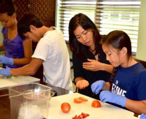 Nghi, center, helps her daughter slice tomatoes at the Pine Manor teen culinary class